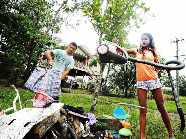 Phyllis Billin (13), of North Lismore, with Aaron Albario (16) cleans out the underneath of her house after floodwaters receded.