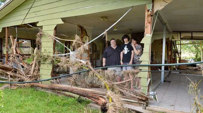 Ian, Maureen and son Bryce Sharkey at their Lower Wonga house destroyed by flood waters.