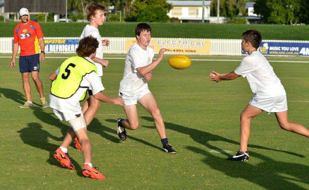 Gold Coast AFL Academy manager Jason Torney runs Mackay players Nick Kemp, Lachlan Baulmer, Beau Saunders and Brayden Harding at Harrup Park.