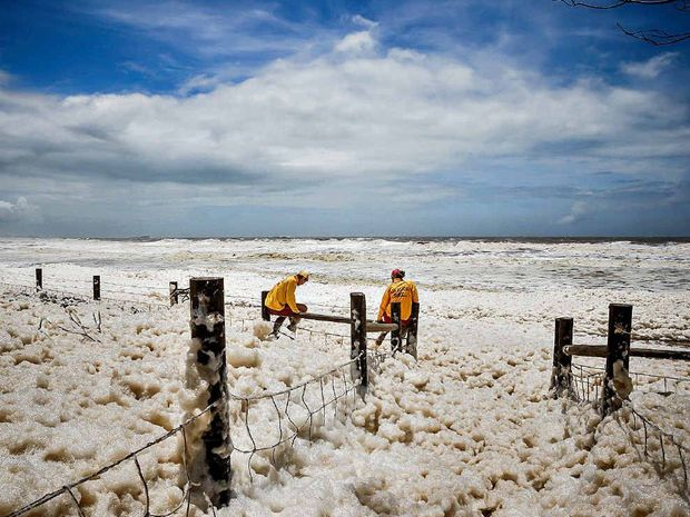 "FROTH AND BUBBLE: Little Mountain photographer Caillin Malley caught two surf lifesavers ""patrolling"" Alexandra Headland's beach froth this week."