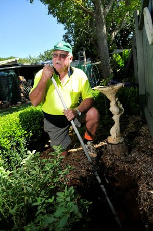 Eaton St resident Robin Musch tests the depth of a chasm that opened in his backyard after last week's storms.