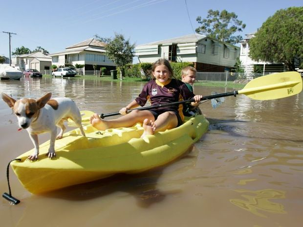Louise and Jacob Watson with freckles the dog outside their grandmothers home in Depot Hill as the Fitzroy River approaches 8.6m in February this year. Grandmother bought kayak after last flood so she could get to the shops.