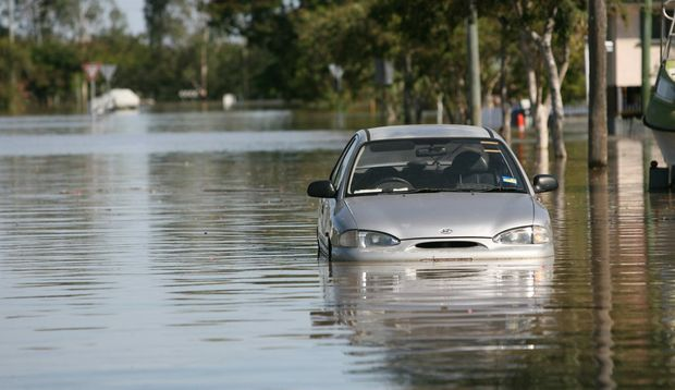 A car sits in flood water in Depot Hill as the Fitzroy River approaches 8.6m. Photo: Chris Ison / The Morning Bulletin