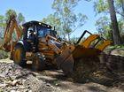 Excavators clearing debris blocking the road.
