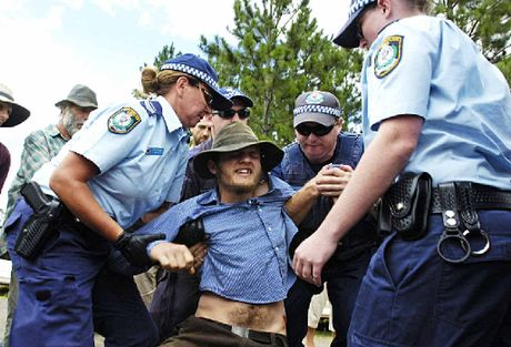 ABOVE: Protester Culley Palmer gets arrested by police at the Doubtful Creek CSG site. TOP: Police escort a truck from the Doubtful Creek CSG mining site.