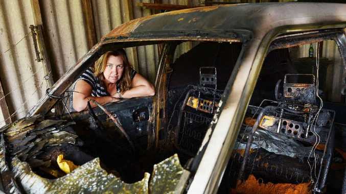 DEVASTATED: Wendy O'Donnell of Lismore with her car that was stolen and found burnt out.