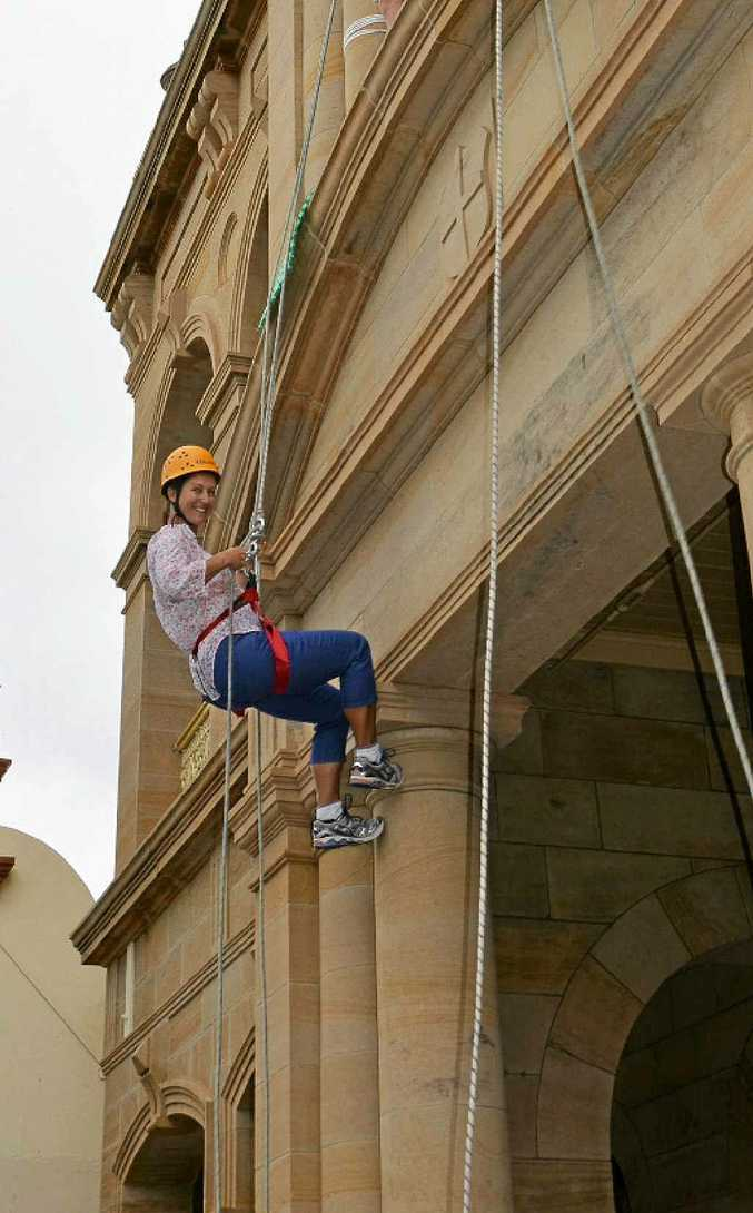 PIECE OF CAKE: Cr Jo McNally scales the facade of the Warwick Town Hall, in support of the scouts.