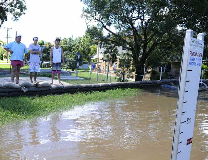 OVERFLOW: Angus McDonald, Nick Crispin and Alex Cole check the flood heights at the Fry St levee.Photo: JoJo Newby