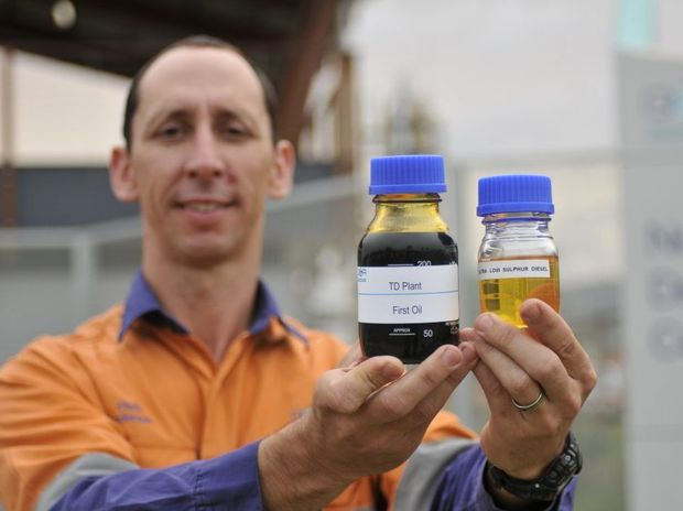 QER general manager Chris Anderson showcases the company's first bottle of oil from a demonstration plant near Fishermans Lane, Gladstone, in 2011.