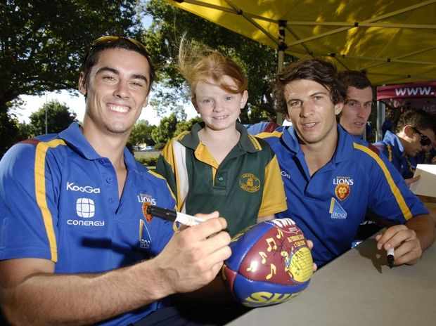Emily Borey has her ball signed by Jesse O'Brien (left) and Rohan Bewick during the last Brisbane Lions visit to Toowoomba.
