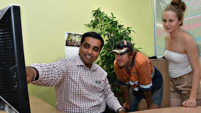 Mackay NAB store manager Younes Chopra talks dollars with Clint Paull and his cousin Vanessa Shelley.