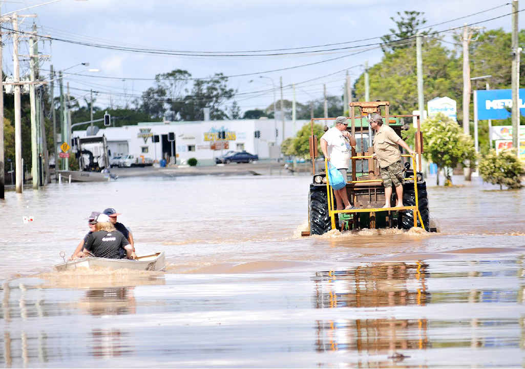 BUNDY BATTLES: People make their way through floodwater in East Bundaberg. About 1200 people stayed in evacuation centres after 2000 homes succumbed to raging floodwater.
