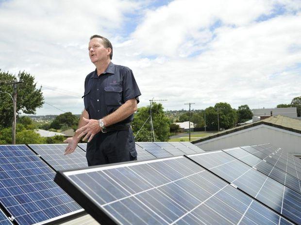 Damien Godsall amongst his five kilowatt, 24-panel solar power system.