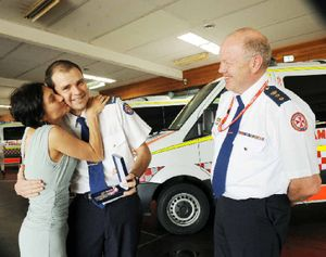 EXTRA PRIZE: Paramedic Gonzalo De Angulo gets a kiss from wife Juliana when receiving his 10 year service medal, as deputy director of operations North Coast chief superintendant Peter Pilon looks on.