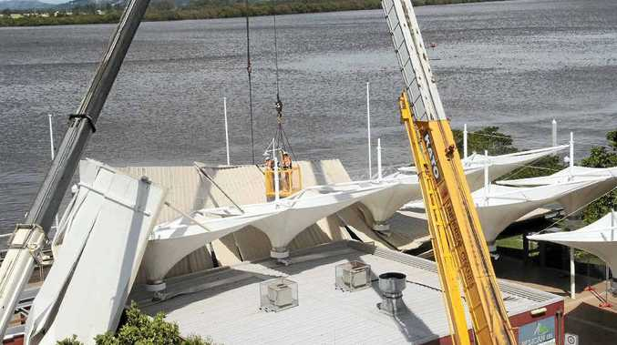 Cranes work to secure the roof of the Pelican restaurant in Ballina, that was torn away by strong winds on Friday.