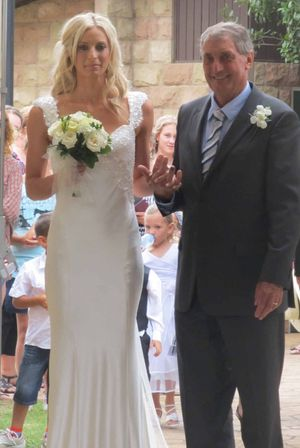 THE ARRIVAL: Proud father Ross Geitz, of Allora, walks Laura down the aisle of The Scots PGC College Chapel.