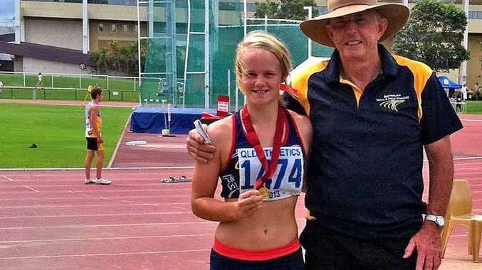 Emily Bass with coach Neil McCoy after winning the under-16 200m hurdles at the Queensland Junior Championships.