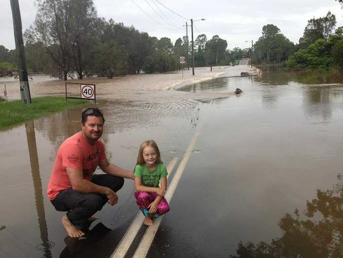 New South Wales visitors Todd and Meg Fisher check out the floodwaters over the Lamington Bridge in Maryborough about 7.30am on Wednesday.
