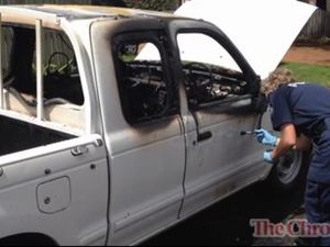Police dust for prints on burnt-out car