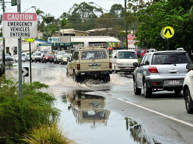 Vehicles negotiate water at Hilton Tce in Tewantin yesterday.