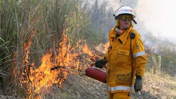 A firefighter from the Cawarral Rural Fire Brigade back burns into a large fast moving bushfire near Mount Charmers.