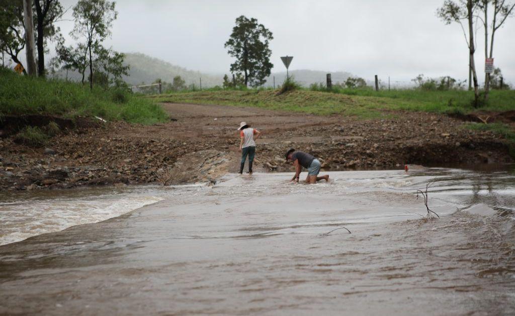 A man checks the depth of a hole on a causeway near Upper Ulam. Photo Allan Reinikka / The Morning Bulletin