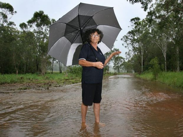 Ekaterini Norman stands in the middle of Hoys Road Coowonga where the heavy rain causing flooding has cut her off from her properties in recent weeks. Photo: Chris Ison / The Morning Bulletin