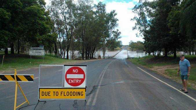 The swollen Condamine river is now running across Condamine's bridge.