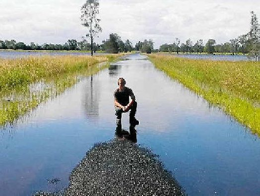 ROAD TO NOWHERE: Bora Ridge resident Jack Wood looking east on Myall Creek Rd, Bora Ridge, which has been flooded for more than 10 days, leaving 30 locals isolated.