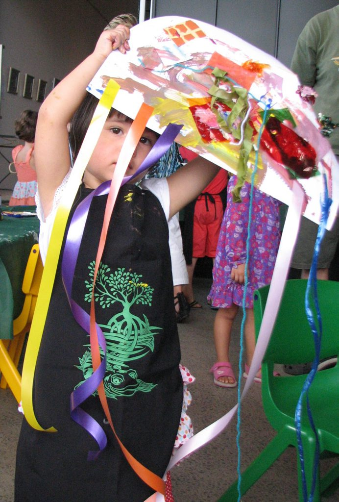 Three-year-old Stella shows off her colourful, collaged jellyfish, created during February's Pipis Club session.