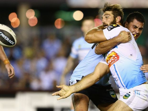 David Taylor of the Titans gets a pass away as he is tackled during the round one NRL match between the Cronulla Sharks and the Gold Coast Titans at Sharks Stadium on March 10, 2013 in Sydney, Australia.