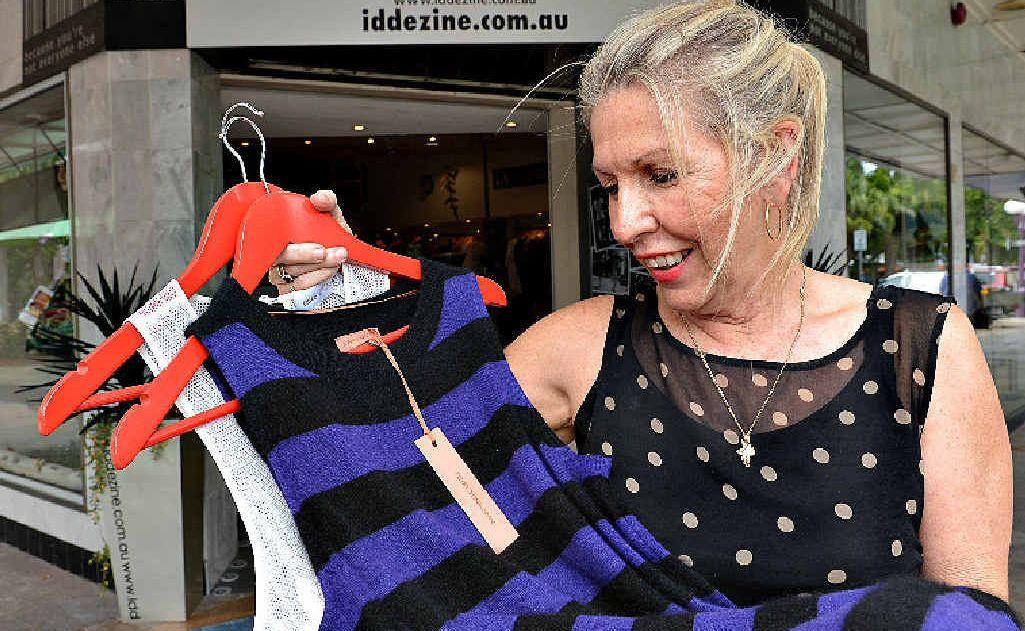 ID Dezine owner Donna Lamprecht prepares red coat hanger sale items for the City Centre Sidewalk Sale.