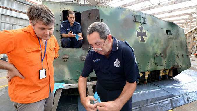 COLD CASE: Police Ballistics Services officer Alan Piper (right) shows a mould taken from the First World War German tank Mephisto to Queensland Museum senior curator Michael Westaway. Police officer Ashley Huth is in the tank with another mould.