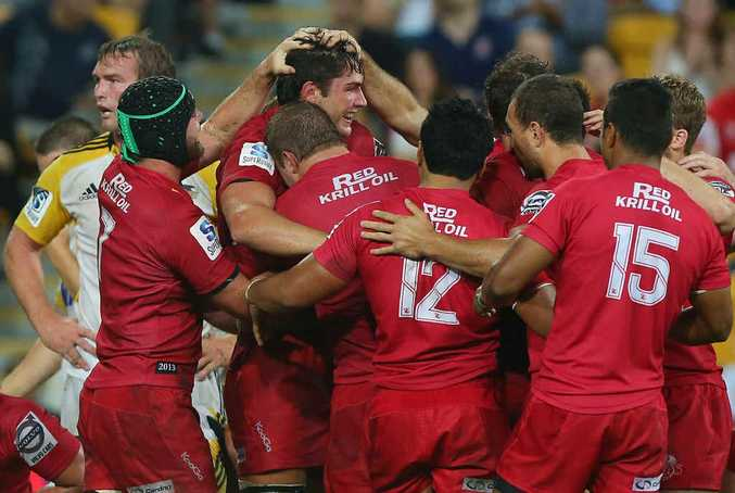 TOP JOB ROB: Reds lock Rob Simmons celebrates with teammates after scoring a try during the Reds' match against the Hurricanes earlier this year.