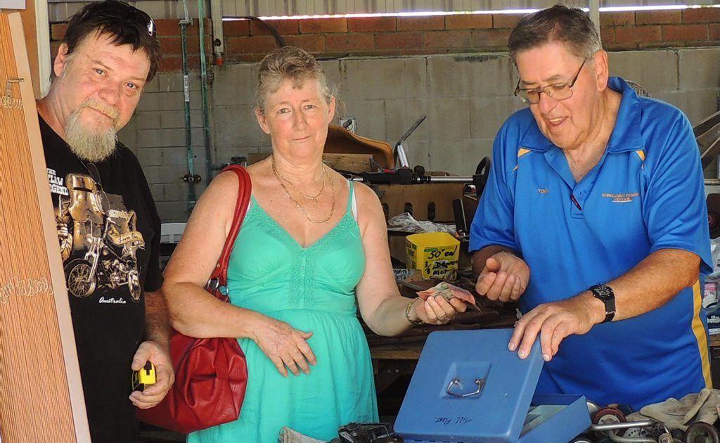Murwillumbah Community Men's Shed vice president Tony Atkinson with happy garage sale customers Carol and Wayne.