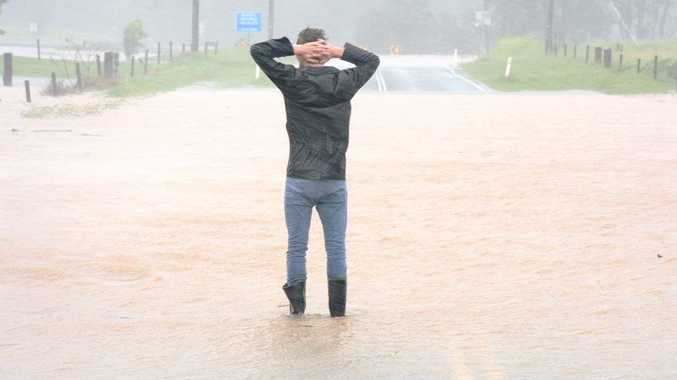 A resident surveys the flood water, which had cut the road off through to Uki by lunchtime on Monday.