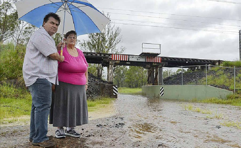 WATER RISING: Janelle Brazier and Cr David Pahlke stand next to pooling rainwater near a rail bridge off Adelong Ave.