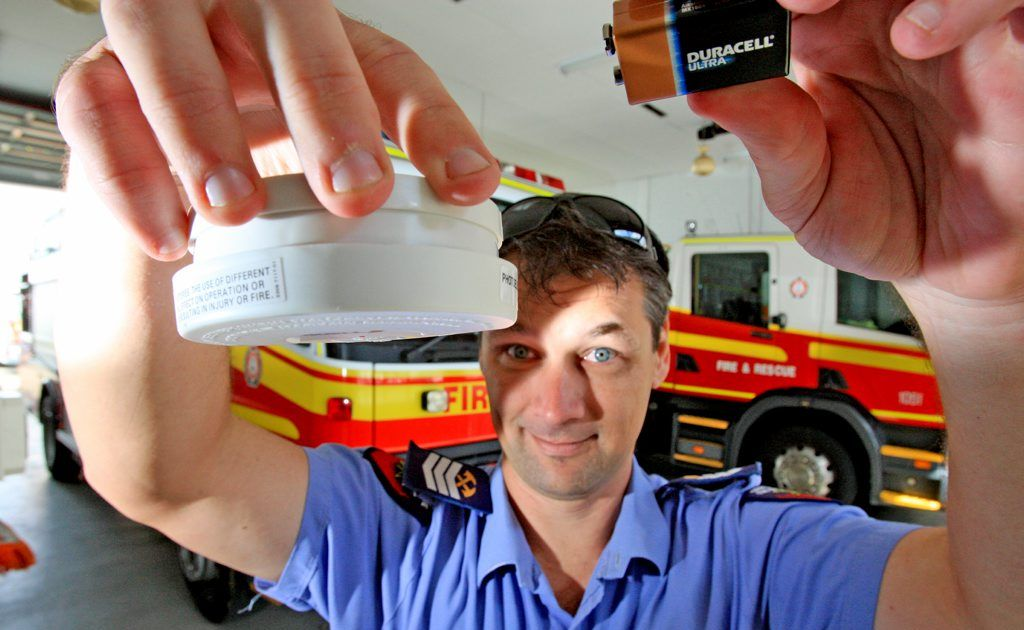 Senior Firefighter Graeme Mitchell with a smoke alarm and fresh battery.