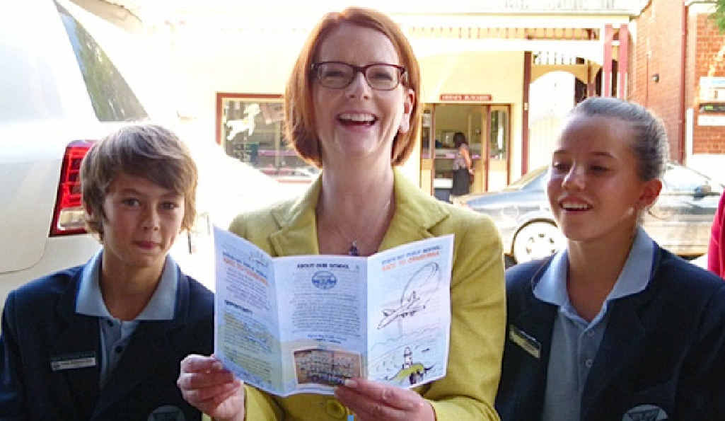 OUR SCHOOL: PM Julia Gillard reads the school brochure to Byron Bay Public School's captains Louis Robinson-Gale and Tia Gotterson.