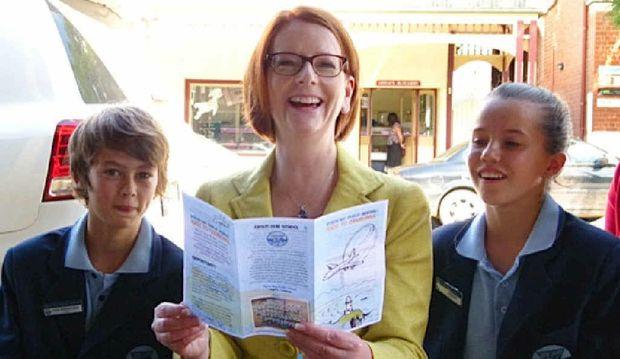 OUR SCHOOL: PM Julia Gillard reads the school brochure to Byron Bay Public School's captains Louis Robinson-Gale and Tia Gotterson.
