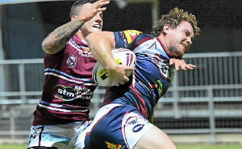 TACKLE TIME: Capras player Brent Williams powers through a tackle by Jordon Grayston in a Capras vs Mackay Cutters game at Browne Park.