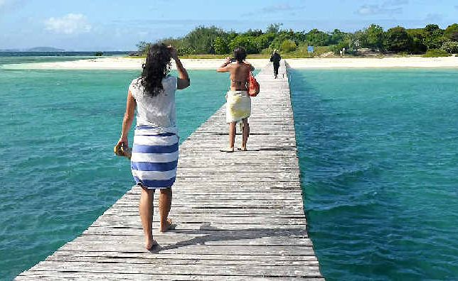 Tourists take a stroll along a pier at the uninhabited Signal Island.