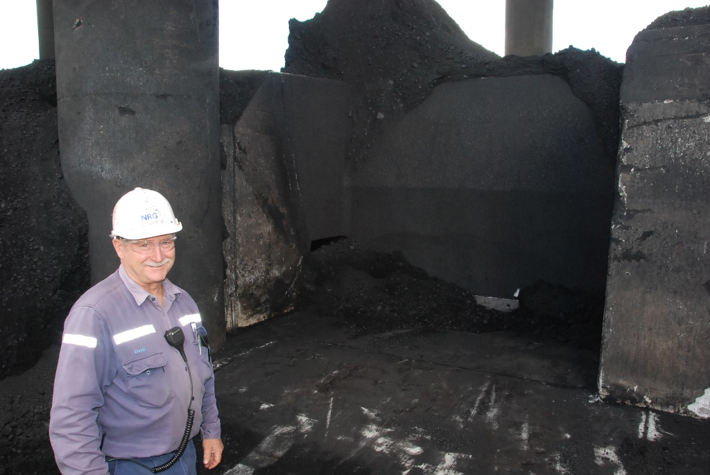 NRG Gladstone Power Station fuel plant operator Dave Brown checks out the recently exposed area of the slot bunker. The area hasn't been seen for decades, but is now visible because coal stockpiles are low after wet weather earlier this year.
