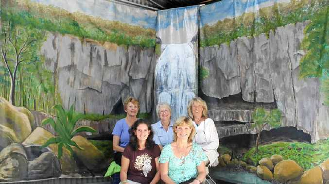 HEALING ART: (front, from left) Alesa Heysmond and Karen Bradley with the Protestors Falls backdrop painted by members of the Village Artists (back, from left) Mary Jacombs, Ros Little and Dors Skinner.