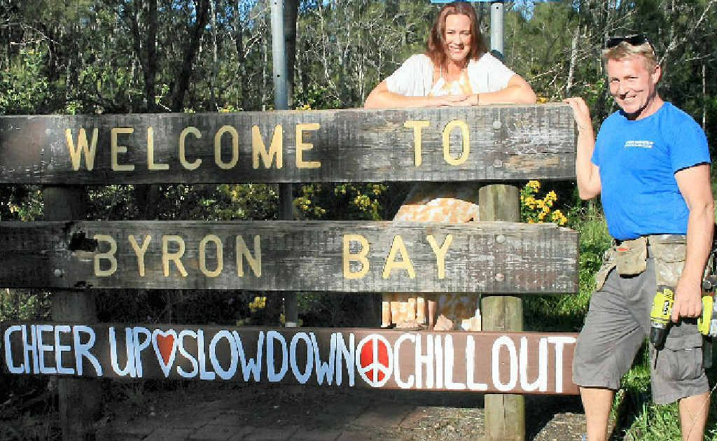 CHILL OUT: The sign is back so we can all relax – Jodie Molloy and Ben Ormonde show off their handiwork on Ewingsdale Rd, Byron Bay.
