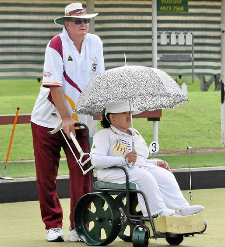 Boyne Tannum Bowls Club secretary Bob Lees assists player Alana Horley during the annual Easter Carnival.