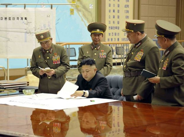 A picture released by the North Korean Central News Agency (KCNA) on 29 March 2013 shows North Korean leader Kim Jong-un (sitting) convening an urgent operation meeting at 0:30 am on 29 March 2013 at an undisclosed location, in which he ordered strategic rocket forces to be on standby to strike US and South Korean targets at any time.