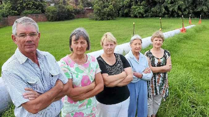 DEJECTED: Steve Mills, Sue Darnell, Colette Dalton, Barbara Epton and Anne McKenzie are not happy about plans to install this 12m high concrete power pole in a council reserve just metres from their homes at Alstonville.