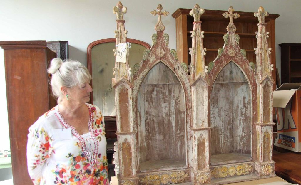 Lorraine Lintern of Uki examines the altar piece from Margaret Olley's Hat Factory, which is in held in the secret storage location.