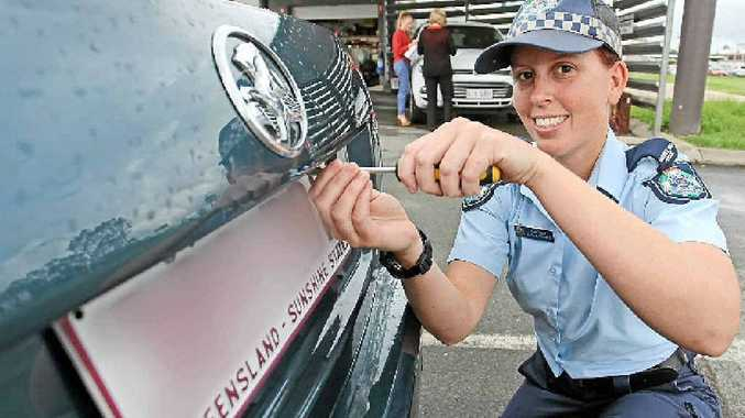 Constable Jessica Dunnett uses one-way screws to make a numberplate more secure.